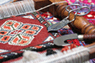 Master weavers using hand spun wool on a loom to create oriental rugs